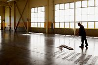 Worker sweeping concrete floor in empty warehouse.