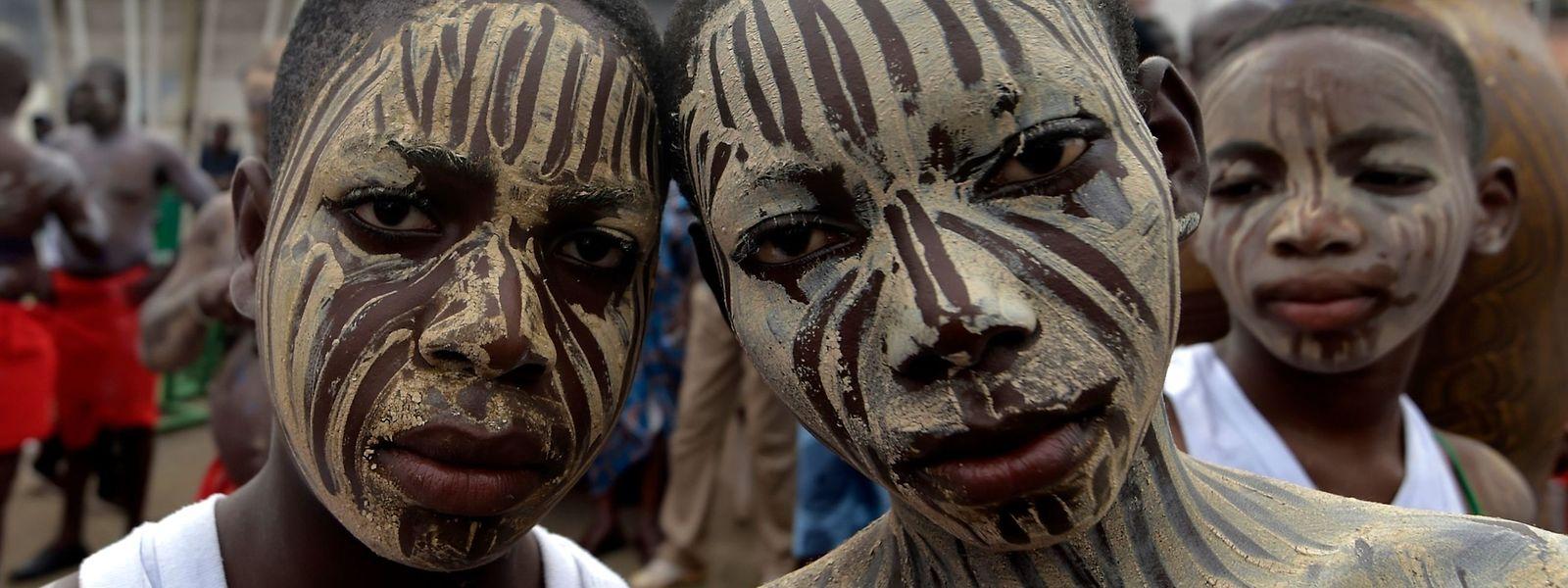"""Abidjan (Elfenbeinküste). Gelebte Tradition: Nach der mit Tanz und Ritualen untermalten """"Fatchue""""-Zeremonie sind die beiden jungen Männer der """"Blessoue Djehou""""-Generation bereit die Geschicke der Dorfgemeinschaft mitzugestalten."""