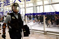 """A policeman secure Terminal 1 after a scuffle with pre-democracy protestors at Hong Kong's International Airport on August 13, 2019. - Hundreds of flights were cancelled or suspended at Hong Kong's airport on August 13 as pro-democracy protesters staged a second disruptive sit-in at the sprawling complex, defying warnings from the city's leader who said they were heading down a """"path of no return"""". (Photo by Manan VATSYAYANA / AFP)"""