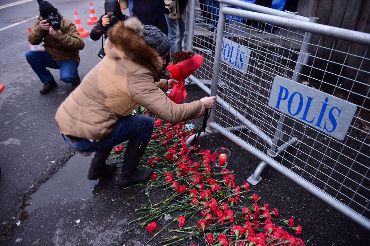 Dimanche en début de soirée, des passants ont déposé des fleurs, d'autres des bougies, sous le regard d'une dizaine de policiers armés de mitraillettes.