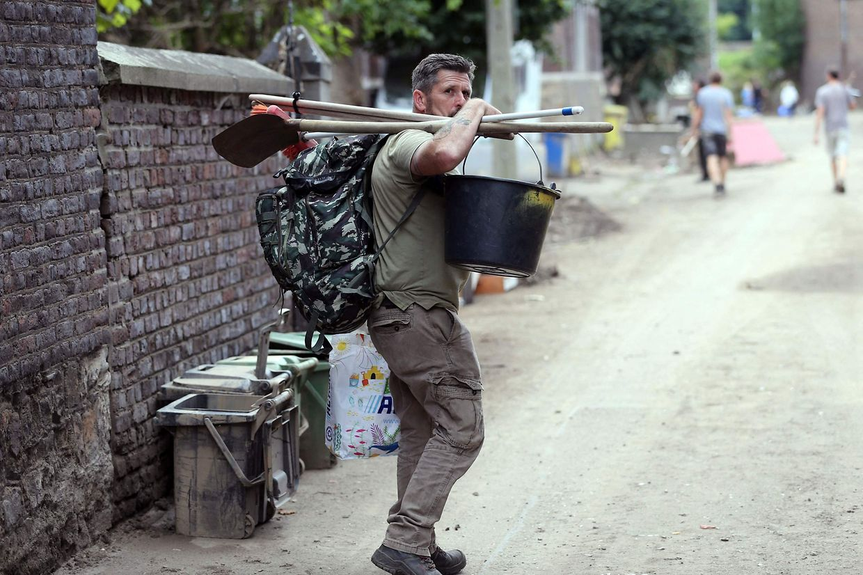 A man carries tools and bucket on July 26, 2021 as clean up work has started in the Belgian town of Trooz, a week after it has been flooded as heavy rains lashed western Europe. - In mid-July western Europe was hit by devastating floods after torrential rains that ravaged entire villages and left at least 209 people dead in Germany and Belgium, as well as dozens missing. Up to two months' worth of rainfall came down in two days in some parts of the region, waterlogging soil that was already near saturation. (Photo by Fran�ois WALSCHAERTS / AFP)