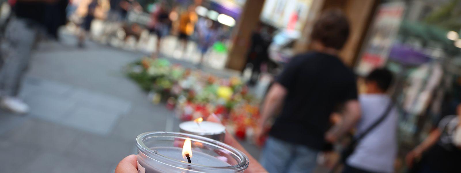 Vor dem Kaufhaus in der Würzburger Innenstadt haben Bürger Kerzen zur Erinnerung an die Opfer aufgestellt.