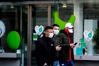 Tourists wear protective face masks as they walk in the centre of Brussels near a closed shop, on March 14, 2020, amid the outbreak of COVID-19, caused by the novel coronavirus. - Belgium close schools, cancel all cultural events and shutter bars and restaurants to stave off the spread of the coronavirus outbreak.  Beginning on March 14, only stores that provide essential services -- such as pharmacies and grocery stores-- will remain open under normal conditions. (Photo by Kenzo TRIBOUILLARD / AFP)