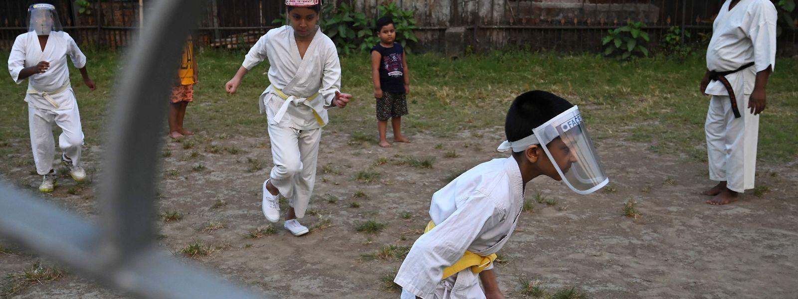 Crianças com viseiras contra a pandemia durante uma aula de artes marciais em Kolkata, na Índia.