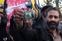 Ein Iraner verbrennt aus Protest einen Dollarschein.