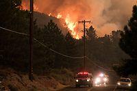 12.08.2020, USA, Lake Hughes: Fahrzeuge der Feuerwehr fahren auf einer Straße nahe eines brennenden Waldstück am Lake Hughes im Angeles Nation Forest. Foto: David Crane/Orange County Register via ZUMA/dpa +++ dpa-Bildfunk +++