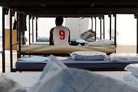ARCHIV - Ein Flüchtling sitzt am 10.10.2014 in München (Bayern) in einem Unterkunftszelt am Internationalen Jugendübernachtungscamp am Kapuzinerhölzl in seinem Bett.    (zu «dpa-Umfrage in den Bundesländern zur Flüchtlings- unterbringung» vom 04.01.2017) Foto: Tobias Hase/dpa +++(c) dpa - Bildfunk+++