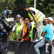 French gendarmes speak with protesters wearing yellow vests (gilets jaunes in French) as they block the traffic on the sixth day of a movement against high fuel prices which has mushroomed into a widespread protest against stagnant spending power under French President on November 22, 2018 in Sainte-Marie on the French overseas island of La Reunion. (Photo by Richard BOUHET / AFP)