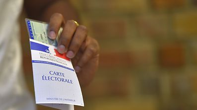 TOPSHOT - A woman holds her electoral card at a polling station in Nantes, western France, during the second round of the French parliamentary elections (elections legislatives in French), on June 18, 2017.  / AFP PHOTO / LOIC VENANCE