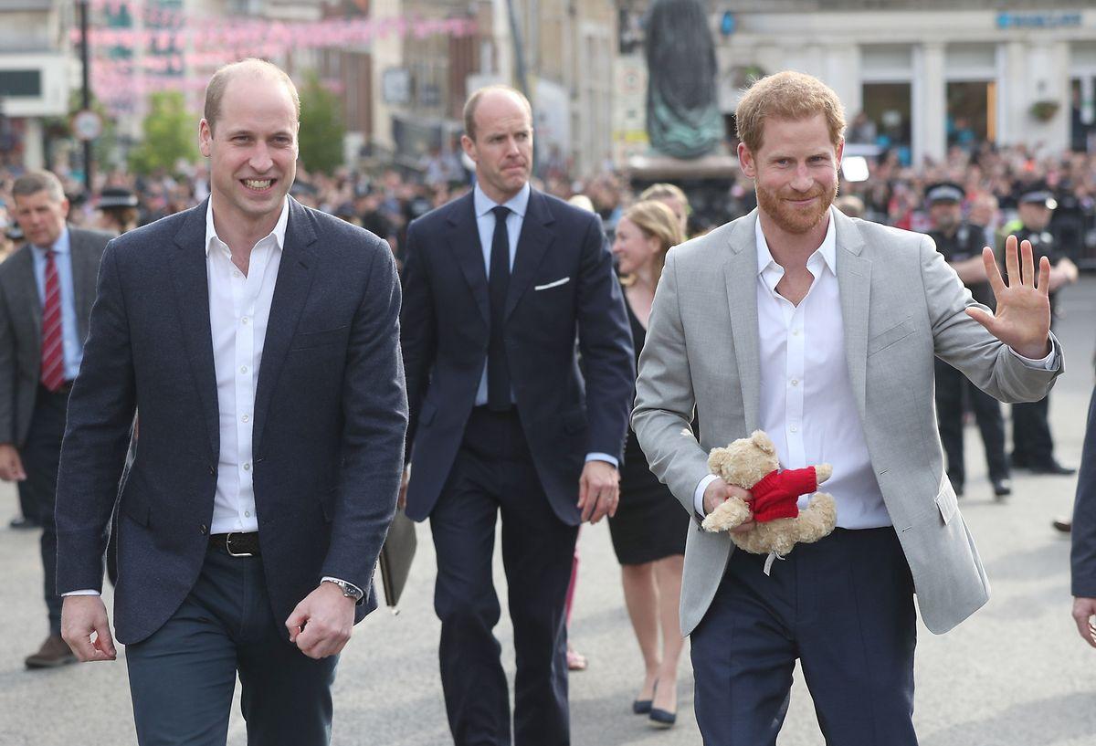 Die britischen Prinzen Harry (r) und William (l) begrüßen Menschen, die im Vorfeld der Royal-Hochzeit vor Schloss Windsor stehen.