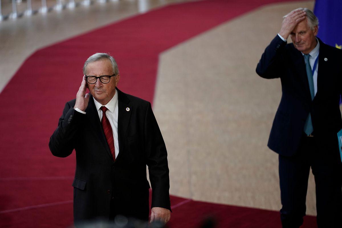 """Augen zu und durch: Kommissionspräsident Jean-Claude Juncker und Brexit-Chefverhandler Michel Barnier bewegen sich durch die """"Journalistenkurve"""" vor dem EU-Ratsgebäude in Brüssel."""