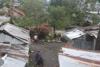 TOPSHOT - People stand by damaged houses and fallen trees on April 25, 2019 in Moroni after tropical storm Kenneth hit Comoros before heading to recently cyclone-ravaged Mozambique. - Cyclone Kenneth passed the Indian Ocean archipelago nation Comoros today but its effects, including high winds and heavy rains, were still being felt, the country's Meteorological Office wrote on Facebook. (Photo by Ibrahim YOUSSOUF / AFP)