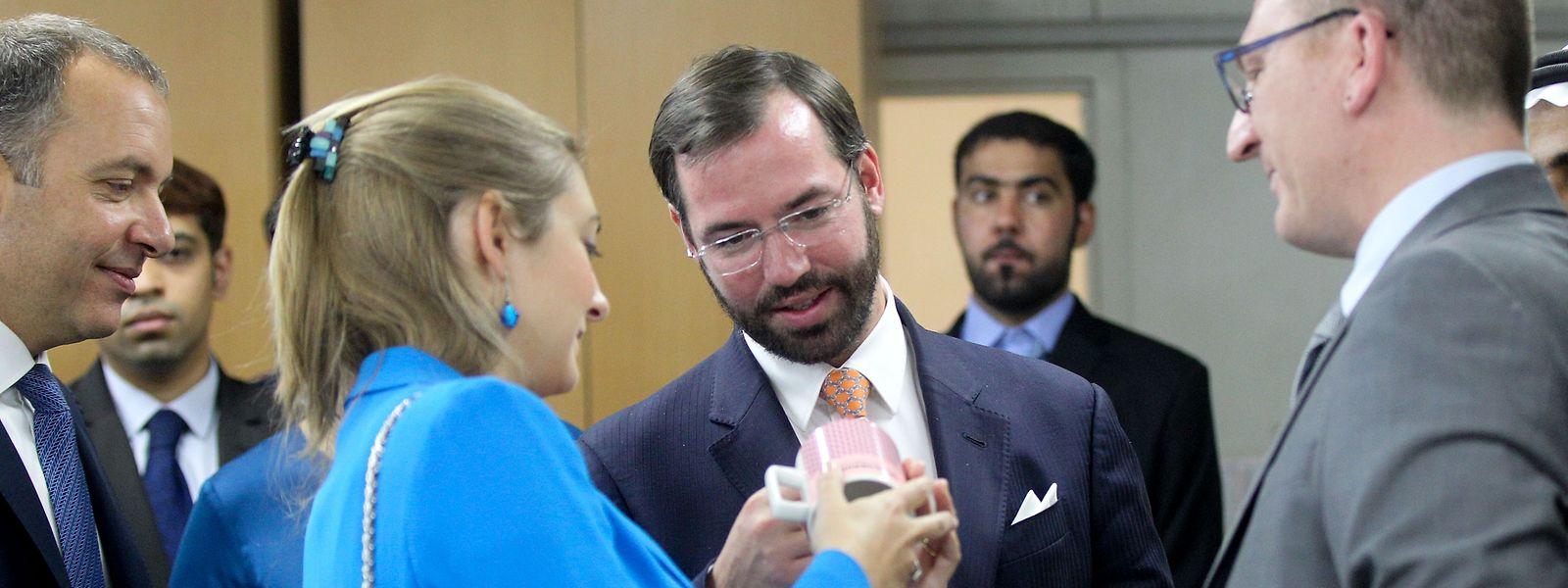 Prinz Guillaume und seine Frau Stéphanie schauen sich die eben gefertigte Nation-Branding-Tasse ganz genau an.