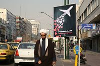"""An Iranian cleric walks past a poster honouring the victims of a Ukrainian passenger jet accidentally shot down in the capital last week, in front of the Amirkabir University in the capital Tehran, on January 13, 2020. - Iran's government denied a """"cover-up"""" after it took days for the armed forces to admit a Ukrainian airliner was shot down by mistake shortly after it took off from Tehran last week, killing all 176 passengers and crew. The plane was brought down hours after Iran had launched missiles at US troops stationed at Iraqi bases, in retaliation for the killing of a top Iranian general. (Photo by ATTA KENARE / AFP)"""
