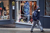 A pedestrian wearing a face mask or covering due to the COVID-19 pandemic, walks past a shop, temporarily closed down due to current coronavirus restrictions, in Shrewsbury, western England on January 6, 2021, on the second day of Britain's national lockdown to combat the spread of COVID-19. - England went back into full lockdown as Europe battled Wednesday to stem a rising tide of coronavirus cases, and the United States logged its worst daily death toll of the pandemic. (Photo by Paul ELLIS / AFP)
