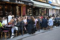 People sit on outside terraces, in Paris, on May 19, 2021 as cafes, restaurants and other businesses re-opened as part of an easing of the nationwide lockdown due to the Covid-19 pandemic. - The French made their way back to cafes and prepared long-awaited visits to cinemas and museums as the country loosened restrictions in a return to semi-normality after over six months of Covid-19 curbs. Cafes and restaurants with terraces or rooftop gardens can now offer outdoor dining, under the second phase of a lockdown-lifting plan that should culminate in a full reopening of the economy on June 30. (Photo by Bertrand GUAY / AFP)