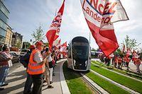 Coups de sifflet, haut-parleurs et pancartes lors de l'arrivée du tramway.