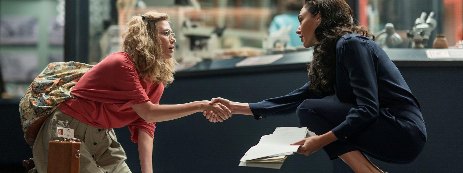 """Die für ihre Auftritte in der Comedy-Show """"Saturday Night Live"""" mehrfach mit einem Emmy ausgezeichnete Schauspielerin Kristen Wiig (l.) schlüpft in """"Wonder Woman 1984"""" in die Rolle der Wissenschaftlerin Barbara Ann Minerva. Sie wird – mit übernatürlichen Kräften ausgestattet – zur Gegenspielerin von Superheldin Wonder Woman (Gal Gadot, r.)."""