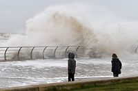 Children play stand near the sea wall with overtopping waves on the promenade in Blackpool, northern England, on February 10, 2020 as high winds brought by Storm Ciara continue. - Storm Ciara grounded hundreds of flights Monday and left swatches of Europe without power after unleashing torrential rain and causing flash flooding that cancelled football matches in Britain. (Photo by Paul ELLIS / AFP)