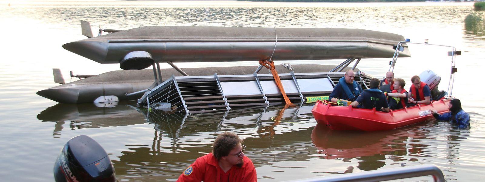 Helfer in Booten mussten Passagiere und Besatzung des gekenterten Katamarans aus dem Wasser retten.