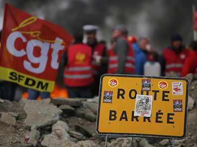 French CGT labour union employees stand near a burning barricade to block the entrance of the fuel depot of the SFDM company near the oil refinery of Donges, France, May 25, 2016 over proposed new labour laws. REUTERS/Stephane Mahe