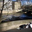 (FILES) In this file photo taken on December 28, 2017 a homeless man sleeps along the river Seine in front of the Saint-Louis island in Paris.  'Near 3,000' homeless people were accounted for in Paris on February 15 and February 16, 2018 during a census to estimate the size of the homeless population, according to the Paris city hall on February 21, 2018.  / AFP PHOTO / Eric FEFERBERG