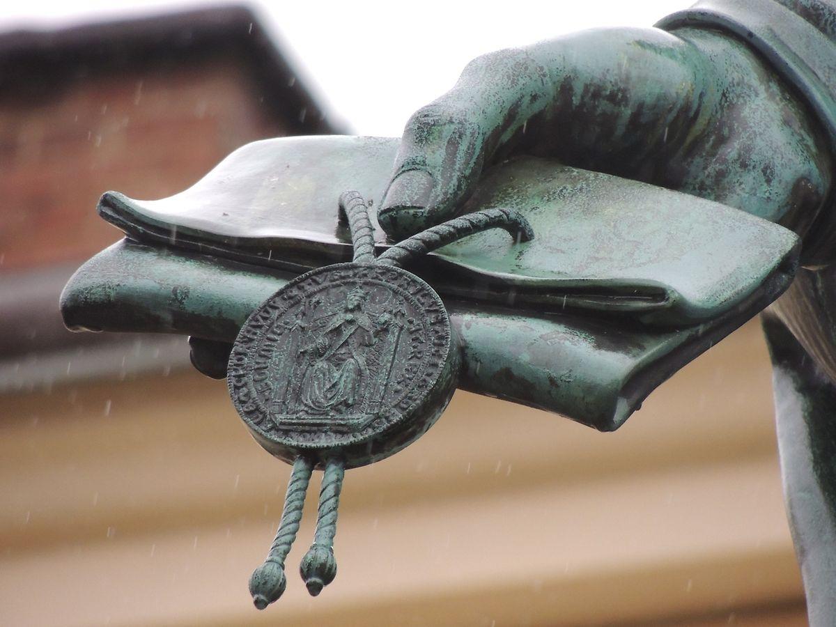Detailansicht des Monumentes von Karl IV. am Fuße der Karlsbrücke: die Gründungsbulle der Prager Universität.