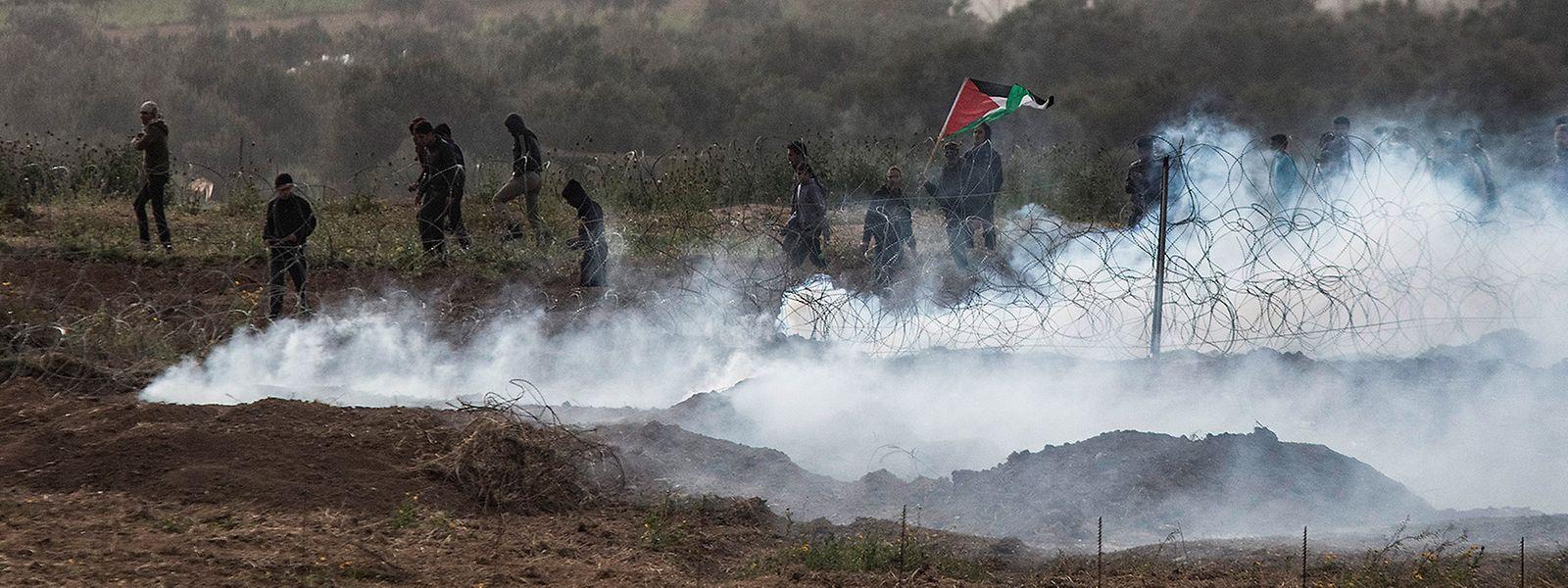 Ein Foto von der israelischen Seite der israelisch-palästinensischen Grenze im Gazastreifen zeigt palästinensische Demonstranten, die inmitten von Tränengas stehen, das von den israelischen Streitkräften während der Zusammenstöße am ersten Jahrestag der Proteste zum Großen Marsch der Rückkehr abgefeuert wurde.