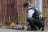 19.04.2019, Großbritannien, Londonderry: Eine Polizistin legt Blumen an den Tatort, wo eine 29-jährige Journalistin bei gewaltsamen Ausschreitungen mit einem Kopfschuss getötet wurde. Am späten Donnerstagabend wurden mehr als 50 Brandsätze auf Polizisten geschleudert. Ein Unbekannter soll Schüsse abgefeuert haben, von denen Augenzeugen zufolge einer die Journalistin traf. Der Tod der 29-Jährigen im Wohngebiet Creggan am Stadtrand sei wohl ein «terroristischer Vorfall», teilte die Polizei am 19.04.2019 mit. Foto: Brian Lawless/PA Wire/dpa +++ dpa-Bildfunk +++