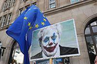 """19.10.2019, Großbritannien, London: Ein Demonstrant trägt ein Plakat, auf dem der britische Premierminister Johnson als Comicfigur """"Der Joker"""" abgebildet ist, während eines Protestmarschs unter dem Titel """"Let Us Be Heard"""". Das britische Parlament ist am Samstagvormittag zu einer historischen Sondersitzung zusammengekommen, um über das zwischen London und Brüssel vereinbarten Brexit-Abkommen abzustimmen. Der britische Premierminister Johnson verfügt über keine Mehrheit im Unterhaus; er muss um jede Stimme kämpfen. Foto: Andrew Matthews/PA Wire/dpa +++ dpa-Bildfunk +++"""