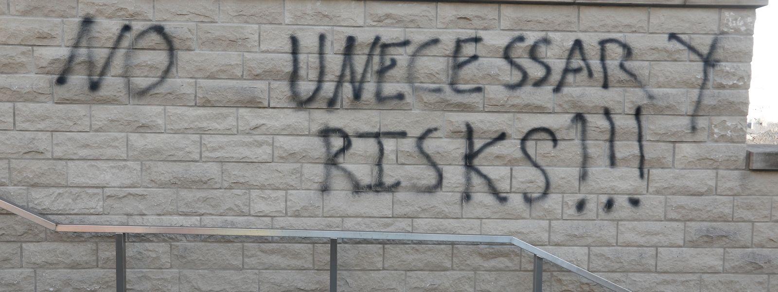 """Vorerst unbekannte Täter haben Graffitis mit Schriftzügen wie """"No unecessary (sic!) risks!"""" und """"We are not your puppets"""" an der Sporthalle des Athénee angebracht."""