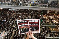 TOPSHOT - CORRECTION - Pro-democracy protesters gather against the police brutality and the controversial extradition bill at Hong Kong's international airport on August 12, 2019. - Hong Kong airport authorities cancelled all remaining departing and arriving flights at the major travel hub on August 12, after thousands of protesters entered the arrivals hall to stage a demonstration. (Photo by Manan VATSYAYANA / AFP) / CORRECTING THE WHOLE CAPTION