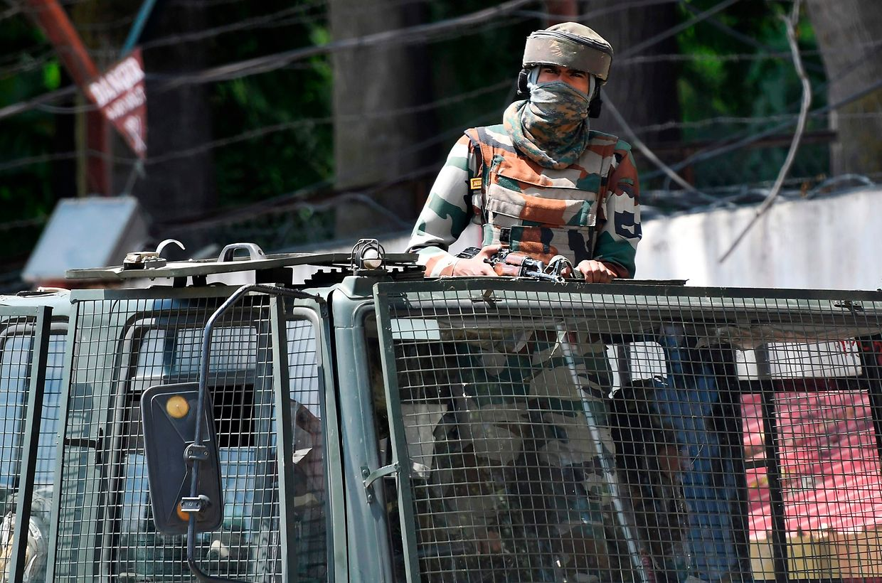 An Indian army soldier stands alert in a truck while travelling in a convoy in Srinagar on August 18, 2019. - Thousands of people have been detained in Indian Kashmir over fears of unrest since New Delhi stripped the restive region of its autonomy two weeks ago, government sources told AFP. A magistrate speaking to AFP on condition of anonymity said at least 4,000 people were arrested and held under the Public Safety Act (PSA), a controversial law that allows authorities to imprison someone for up to two years without charge or trial. (Photo by Punit PARANJPE / AFP)