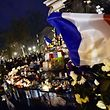 TOPSHOTS A French flag flutters over candles and flowers as people gather at Place de la Republique (Republic Square) in Paris on November 22, 2015 to pay tribute for the victims of the November 13 terror attacks. A coordinated wave of attacks on Parisian nightspots claimed by Islamic State group (IS) jihadists killed 130 people. AFP PHOTO / LOIC VENANCE