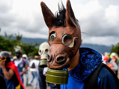 TOPSHOT - A masked Venezuelan opposition activist takes part in a march against President Nicolas Maduro, in Caracas on May 1, 2017. Security forces in riot vans blocked off central Caracas Monday as Venezuela braced for pro- and anti-government May Day protests one month after a wave of deadly political unrest erupted.  / AFP PHOTO / FEDERICO PARRA