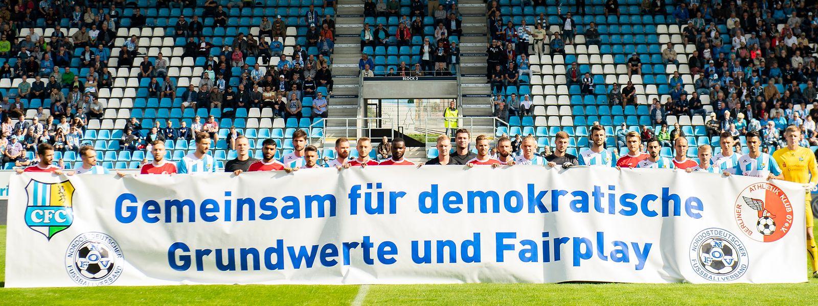 """Die Spieler des Chemnitzer FC und des Berliner AK hielten vor Beginn des Spiels ein Banner mit der Aufschrift """"Gemeinsam für demokratische Grundwerte und Fairplay""""."""