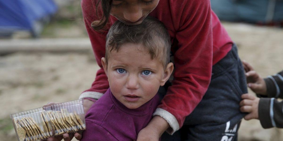 Ein Kind füttert ein anderes Kind in einer provisorischen Zeltstadt für Migranten und Flüchtlinge nahe Idomeni.