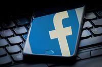 """25.03.2018, Großbritannien, London: Das Logo von Facebook spiegelt sich auf einem Smartphone, das auf der Tastatur eines Laptops liegt. (zu dpa """"Facebook entschuldigt sich in Zeitungsanzeige für Vertrauensbruch"""" vom 27.03.2018) Foto: Dominic Lipinski/PA Wire/dpa +++ dpa-Bildfunk +++"""