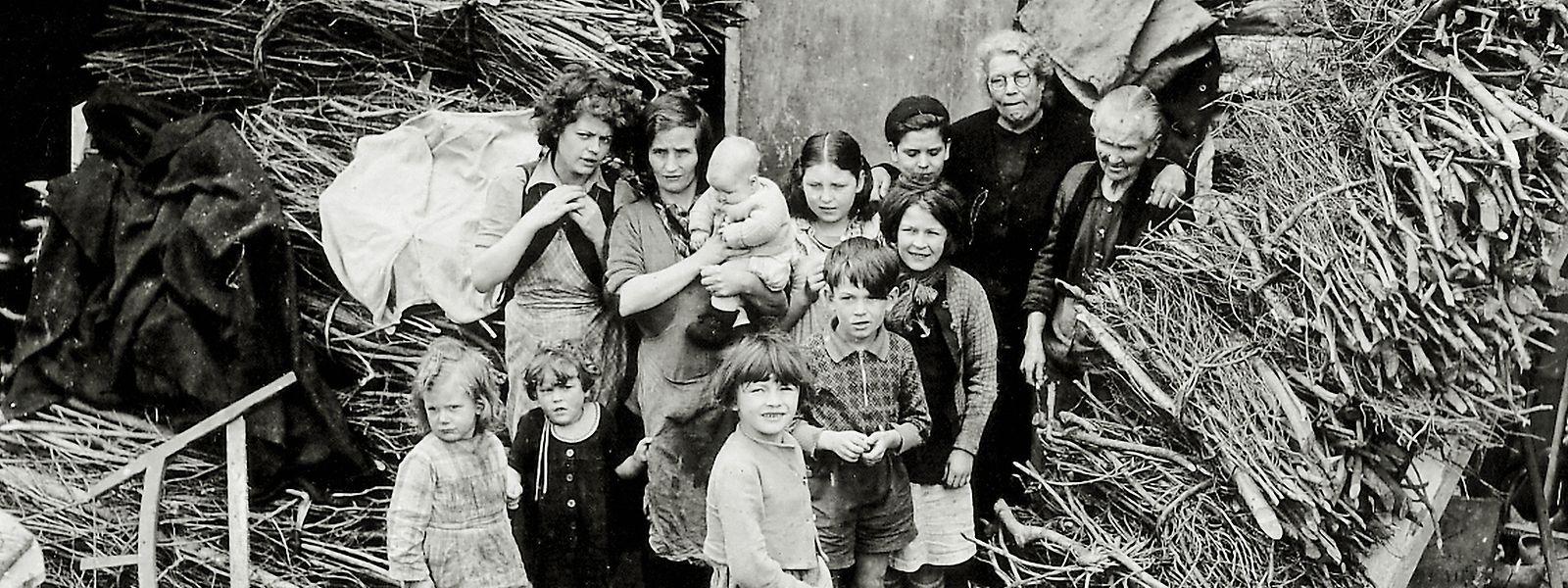 Kinder und Frauen kommen am 26. Juli 1944 in Saint-Lô aus ihren Schutzräumen.