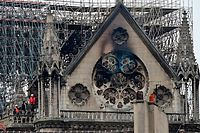 TOPSHOT - Inspectors are seen on the roof of the landmark Notre-Dame Cathedral in central Paris on April 16, 2019, the day after a fire ripped through its main roof. - A major fire broke out at the landmark Notre-Dame Cathedral in central Paris sending flames and huge clouds of grey smoke billowing into the sky, the fire service said. The flames and smoke plumed from the spire and roof of the gothic cathedral, visited by millions of people a year, where renovations are currently underway. (Photo by Lionel BONAVENTURE / AFP)