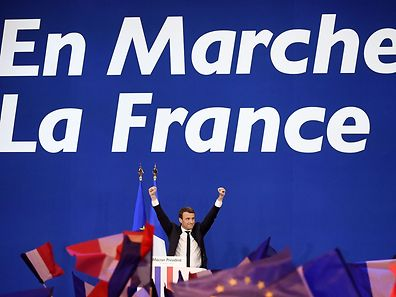 TOPSHOT - French presidential election candidate for the En Marche ! movement Emmanuel Macron waves at the audience during a meeting at the Parc des Expositions in Paris, on April 23, 2017, after the first round of the Presidential election. Centrist Emmanuel Macron and far-right leader Marine Le Pen emerged as the projected winners of a nail-biting first round presidential vote in France. / AFP PHOTO / Eric FEFERBERG