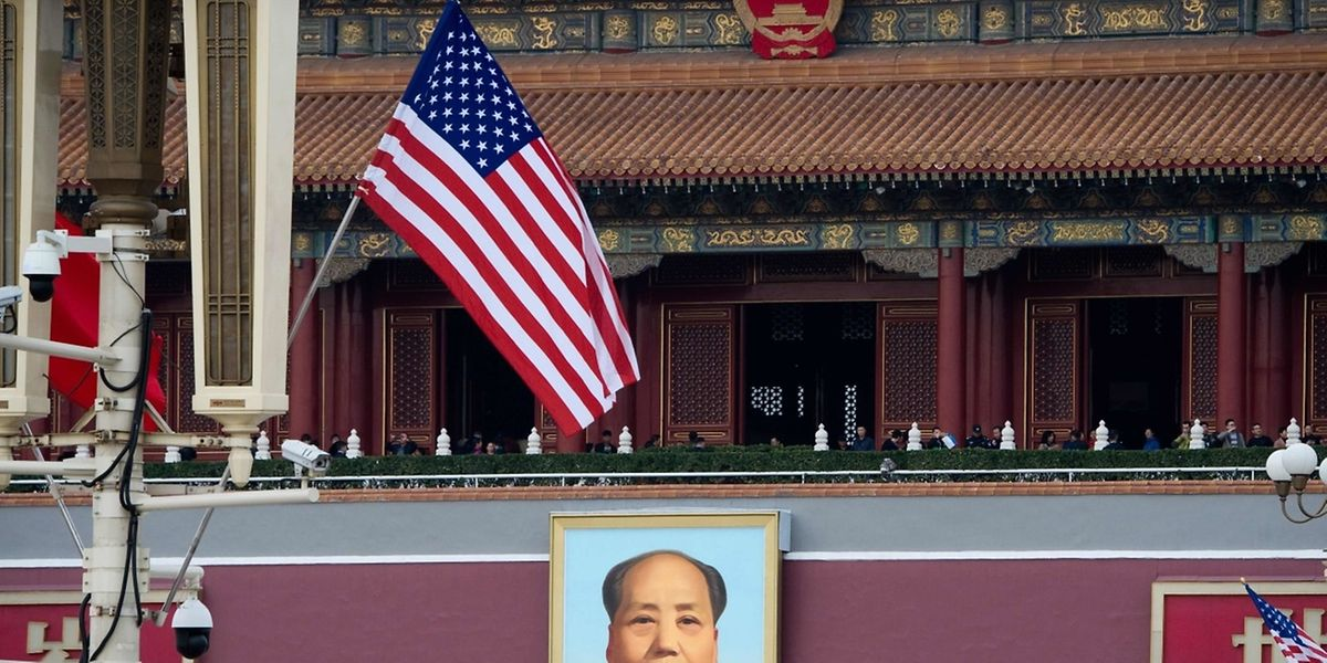 A US flag is displayed in front of the portrait of China's late communist leader Mao Zedong outside the Forbidden City in Beijing on November 8, 2017.  US President Donald Trump toured the Forbidden City with Chinese leader Xi Jinping on November 8 as he began the crucial leg of an Asian tour intended to build a global front against North Korea's nuclear threats. / AFP PHOTO / Nicolas ASFOURI
