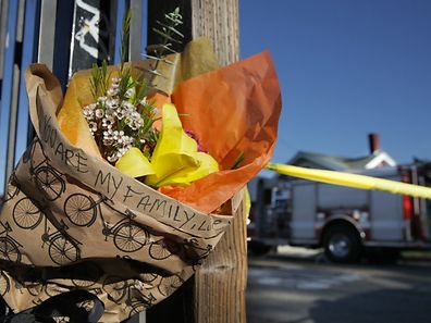 "Flowers bearing the message ""you are my family"" are placed near the scene following an overnight fire that claimed the lives of up to 40"