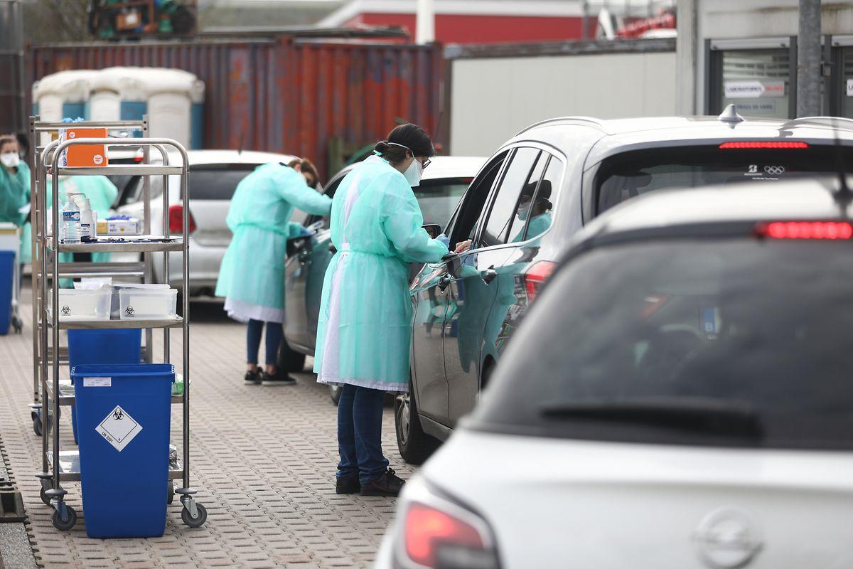 Mitarbeiter einer Drive-in-Teststation in Junglinster nehmen Abstriche von Erkrankten.