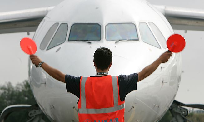 Airport worker guides a plane on the runway