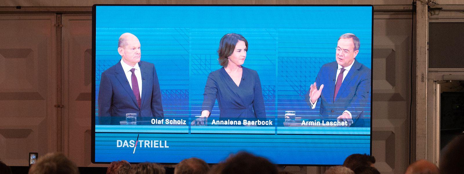 Kanzlerkandidat Olaf Scholz (SPD, l-r), Kanzlerkandidatin Annalena Baerbock (Bündnis90/Die Grünen) und Kanzlerkandidat Armin Laschet (CDU) sind während des Triells auf einem Bildschirm zu sehen.