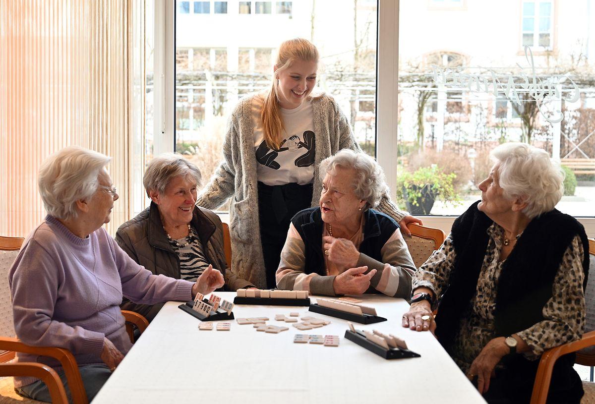 Anne Bourgmeyer unterhält sich während eines Gesellschaftsspiels mit Bewohnerinnen einer Seniorenresidenz in Trier.
