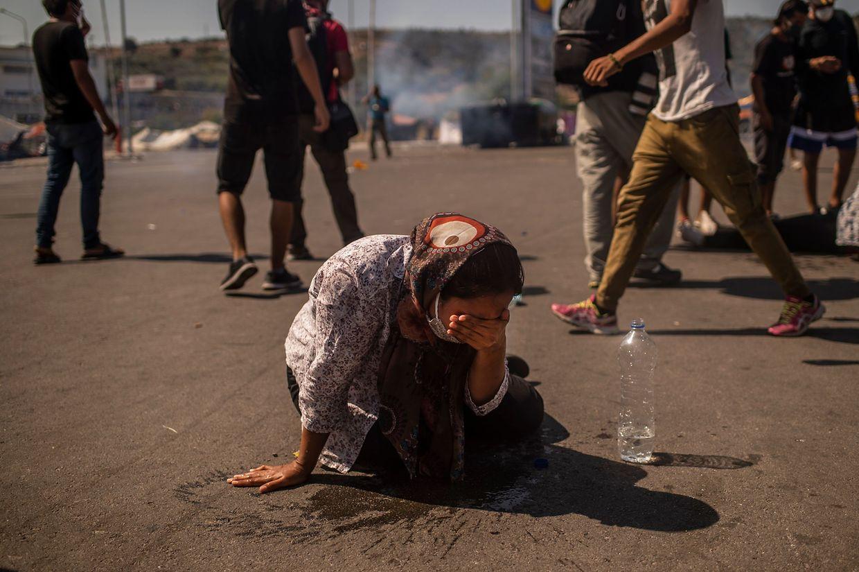 Eine Frau spült sich Tränengas mit Wasser aus den Augen. Auf Lesbos ist es bei Protesten zu Zusammenstößen zwischen Flüchtlingen und Polizei gekommen.