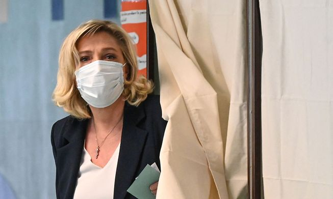 Marine Le Pen leaves a polling booth prior to casting her vote in Henin-Beaumont, northern France, on Sunday