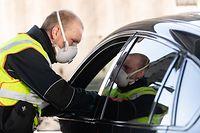 16.03.2020, Baden-Württemberg, Weil am Rhein: Ein Bundespolizist mit Atemmaske kontrolliert am Grenzübergang zur Schweiz ein Fahrzeug. In der Coronavirus-Krise führt Deutschland am Montag umfassende Kontrollen und Einreiseverbote an den Grenzen auch zur Schweiz ein. Foto: Patrick Seeger/dpa +++ dpa-Bildfunk +++